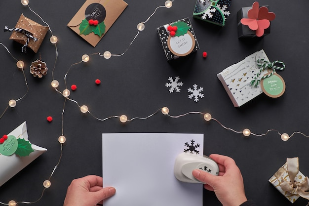 New year or christmas presents in various paper gift boxes with tags. hands making paper snowflakes with hole puncher. festive flat lay, top view with light garland and deco gift boxes on black paper.