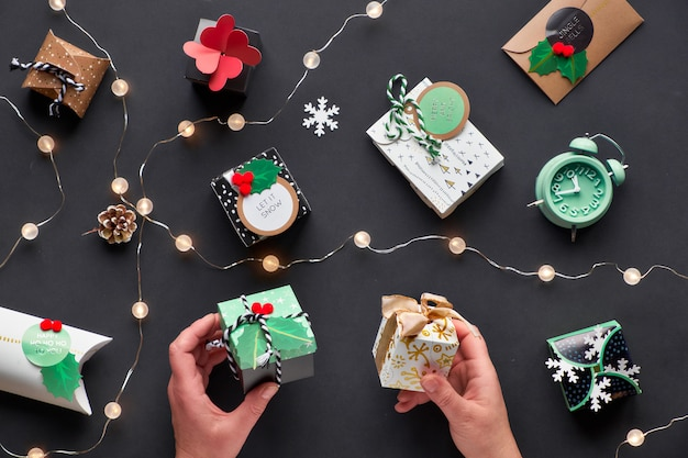 New year or christmas presents wrapped in various paper gift boxes with festive tags. two hands holding boxes. festive flat lay, top view with light garland, alarm clock and snowflakes on black paper.