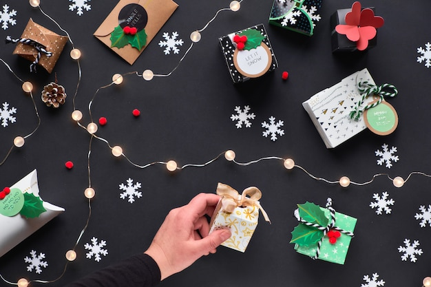 New year or christmas presents wrapped in various paper gift boxes with tags. hand holding box with holly. festive flat lay, top view with light garland, alarm clock and snowflakes on black paper.
