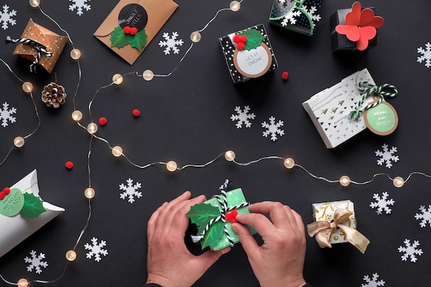 New year or christmas presents wrapped in various paper gift boxes with tags. hands decorating box with green holly. festive flat lay, top view with light garland, alarm and snowflakes on black paper.