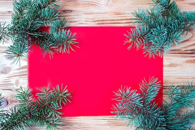 New year and christmas red card on a wooden background with fir branches, flat lay, copy space, mock up.
