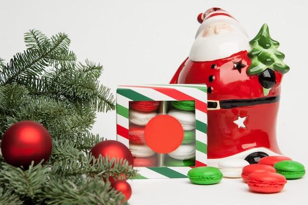クッキーと白い背景の上のクリスマスツリーと新年のクリスマスサンタクロース