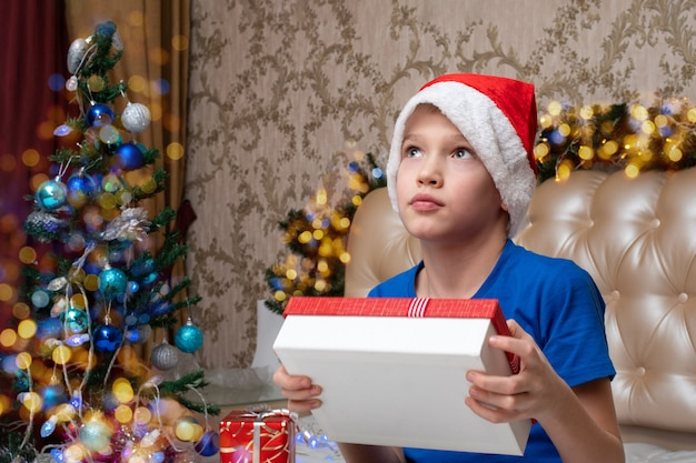 New year and christmas traditions. a cute little boy holding a gift box in his hands at home decorated for christmas. the boy is thinking what gift is in the box