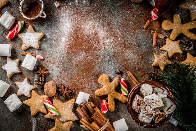 New year, christmas treats. cup of hot chocolate with fried marshmallow, ginger star cookies, gingerbread men, striped candy, spices cinnamon, anise, cocoa, powdered sugar.  top view  frame