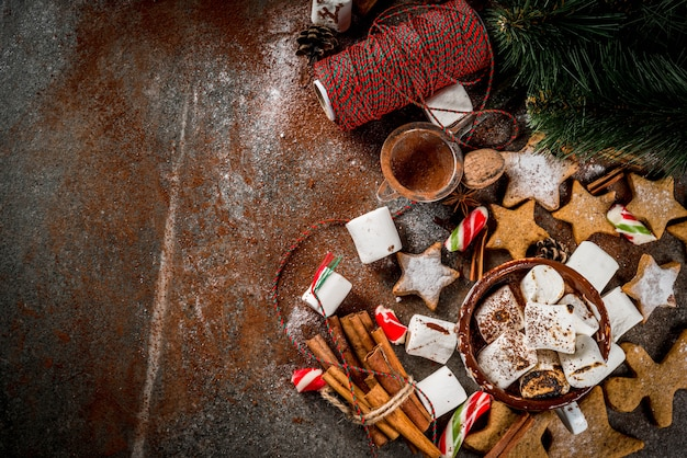 New year, christmas treats, sweets. cup of hot chocolate with fried marshmallow, ginger star cookies, gingerbread men, striped candy, spices cinnamon anise, cocoa, powdered sugar.   top view