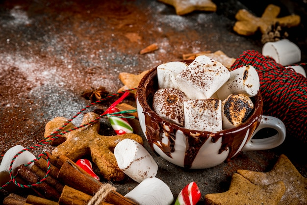 New year, christmas treats, sweets. cup of hot chocolate with fried marshmallow, ginger star cookies, gingerbread men, striped candy, spices cinnamon anise, cocoa, powdered sugar.