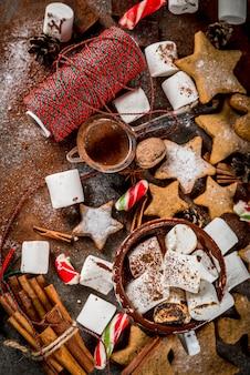 新年、クリスマスのお菓子、お菓子。揚げマシュマロ、ジンジャースタークッキー、ジンジャーブレッド男性、縞模様のキャンディ、スパイスシナモンアニス、ココア、粉砂糖入りのホットチョコレートのカップ。コピースペーストップビュー