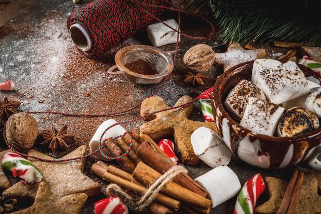 Новый год, новогодние угощения, сладости. чашка горячего шоколада с жареным зефиром, имбирным звездным печеньем, пряничными человечками, полосатыми конфетами, специями, анисом, корицей, какао, сахарной пудрой.