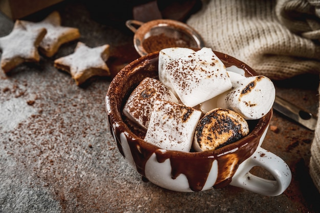 New year and christmas treats. traditional sweets. a cup of hot chocolate with marshmallow fried on fire, gingerbread stars, with sweater on black stone background,