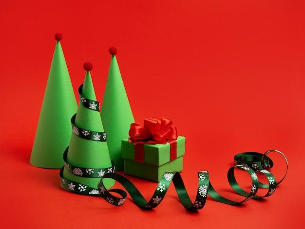 真っ赤な背景のクリスマスの装身具に紙の曲がりくねったギフトで作られた新年のクリスマスツリー
