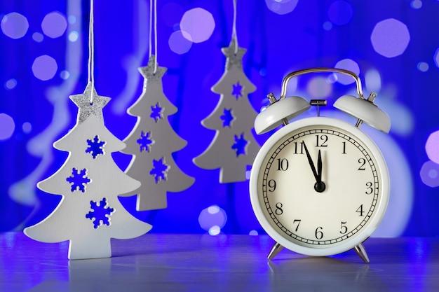 青い背景に装飾が施された新年の時計。明けましておめでとうございます。