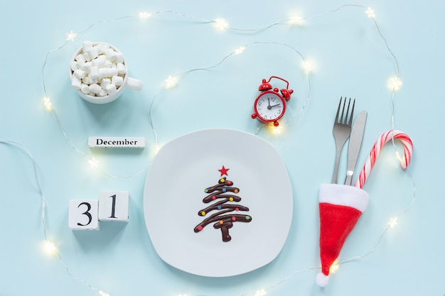 New year composition calendar december 31. sweet chocolate christmas tree on plate, cutlery, cocoa, alarm clock