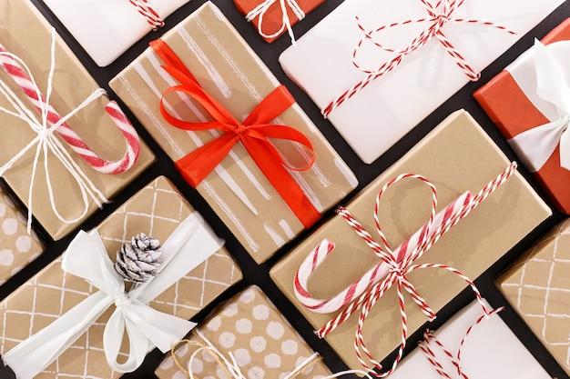 새해 구성. 빨간색, 공예, 흰색 포장 된 선물 상자 컬러 리본 및 로프, 사탕 지팡이, 검은 색 표면에 콘 크리스마스 표면. 겨울 휴가 패턴. 평면도, 평면 누워.