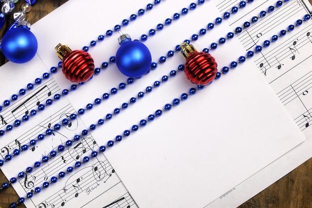 Новогодняя композиция елочные игрушки на столе и листе с нотами