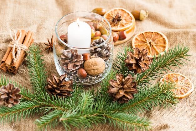 天然成分とトウヒの枝が入ったガラスの瓶の中で燃える白いろうそくの新年の構成。新年の装飾のコンセプト。