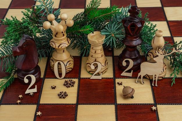 Новогодняя композиция на шахматной доске с ферзем и другими фигурами 2022 г. вид сверху.