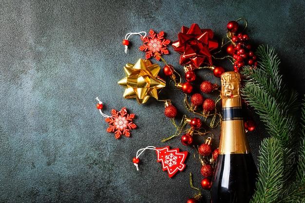 金色のシャンパンボトルとクリスマスの装飾が施された新年の作曲。明けましておめでとうございます。クリスマスフラットレイ。新年2022年。新年のコンセプト
