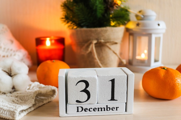 New year composition with wooden calendar candles christmas tree calendar knitted sweater tangerines