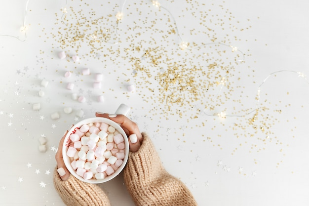 New year concept. cup with hot chocolate and marshmallows in hands on a white background