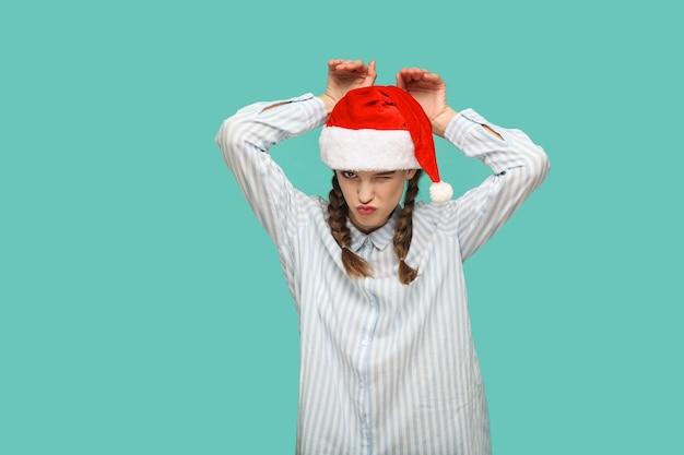 새 해 개념입니다. 빨간 크리스마스 모자를 쓴 줄무늬 밝은 파란색 셔츠를 입은 재미있는 아름다운 소녀가 토끼 제스처, 윙크, 키스, 카메라를 쳐다보며 서 있습니다. 스튜디오 촬영에 고립 된 녹색 배경입니다.
