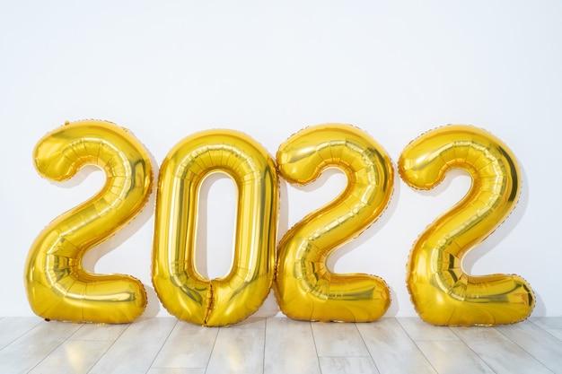 新年のコンセプト。ゴールドパーティーバルーン2022番号は、白い背景、パノラマ、空き領域に形をしています。高品質の写真