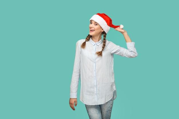 새 해 개념입니다. 줄무늬 밝은 파란색 셔츠를 입은 행복한 재미있는 아름다운 소녀가 서서 빨간 크리스마스 모자를 들고 이빨 미소로 카메라를 바라보고 있습니다. 실내 녹색 배경에 고립입니다.