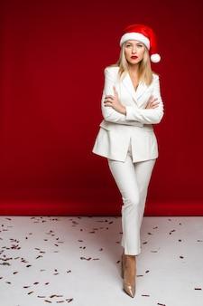 派手なスーツと赤い背景でポーズをとるサンタの帽子のエレガントな女性の新年のコンセプト写真。休日のコンセプト