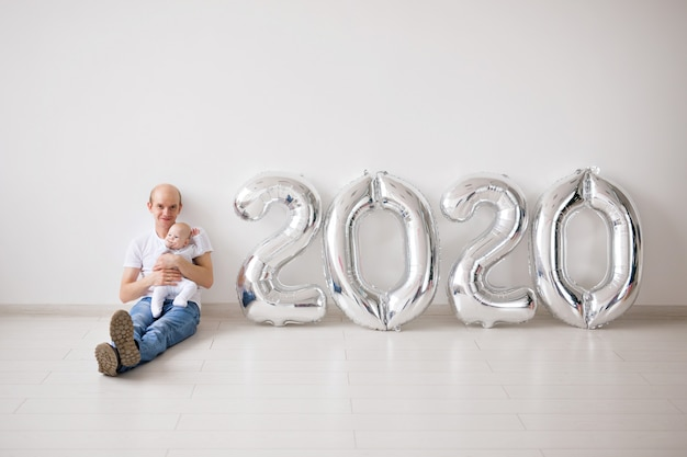 Новогодняя концепция - гордый отец держит новорожденную дочь возле воздушных шаров 2020 года