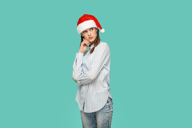 New year concept. thoughtful beautiful girl in striped light blue shirt in red christmas cap standing crossed hands, confused face and thinking. indoor, studio shot isolated on green background.