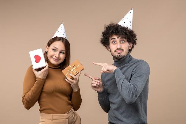 아름 다운 젊은 부부와 함께 새 해 개념 새 해 모자 감정적 인 소녀를 착용