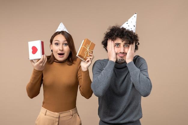 Новогодняя концепция с красивой молодой парой в новогодней шапке счастливая девушка с сердцем и подарком