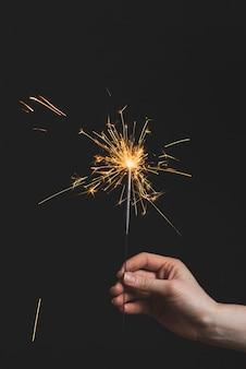Concetto del nuovo anno con lo sparkler della tenuta della mano