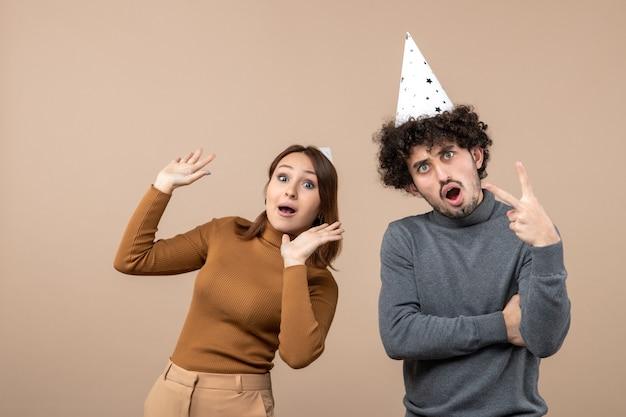 Il concetto del nuovo anno con le giovani coppie felici emozionanti adorabili porta la ragazza ed il ragazzo del cappello del nuovo anno su gray