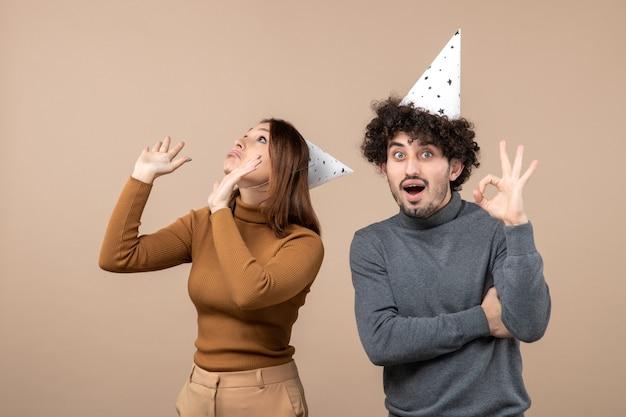 素敵な興奮した幸せな若いカップルが上を見て新年の帽子の女の子を着て新年のコンセプト