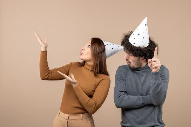 Il concetto del nuovo anno con le giovani coppie felici emozionanti adorabili porta la ragazza del cappello del nuovo anno che osserva sopra
