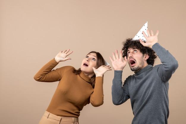 Новогодняя концепция с прекрасной взволнованной счастливой молодой парой в новогодней шапке, смотрящей над девушкой