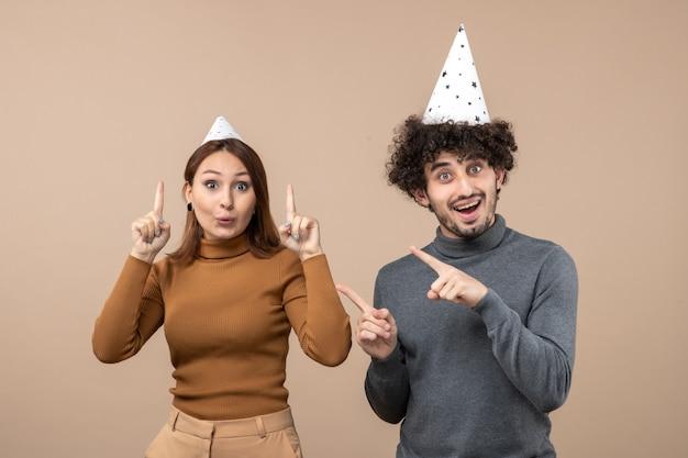 Il concetto di nuovo anno con la giovane coppia spaventata indossa la ragazza e il ragazzo del cappello del nuovo anno su gray
