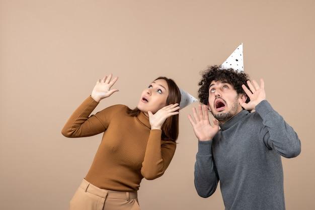 Il concetto di nuovo anno con la giovane coppia spaventata indossa il cappello del nuovo anno guardando sopra la ragazza e il ragazzo scioccati su gray