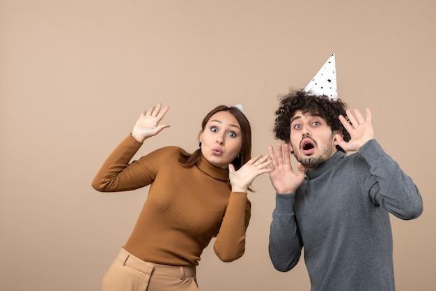 ショックを受けた若いカップルと新年のコンセプトは、灰色の女の子と男を見て新年の帽子をかぶる