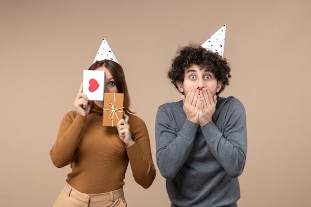 若いカップルが彼女の顔の心と贈り物とショックを受けた男を閉じる新年の帽子の女の子を着て新年のコンセプト