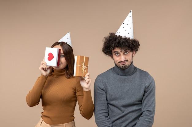 젊은 부부와 함께 새해 개념은 그녀의 얼굴 마음과 선물과 만족하지 않는 사람을 닫는 새해 모자 소녀를 착용