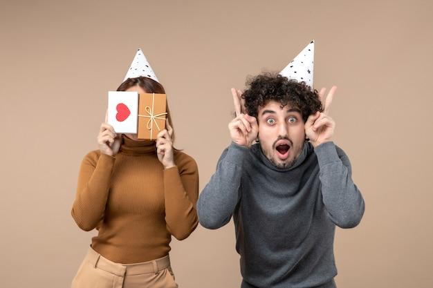 若いカップルが心と贈り物で彼女の顔を閉じる新年の帽子の女の子を着て新年のコンセプト
