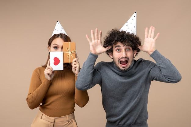 Il concetto di nuovo anno con la giovane coppia indossa la ragazza del cappello del nuovo anno chiudendo il viso con il cuore e il regalo e il ragazzo che mostra dieci su grigio