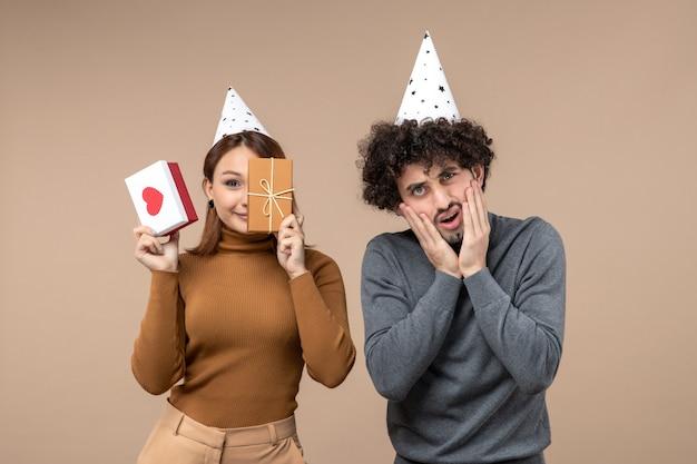 若いカップルが彼女の半分の顔の心と贈り物を閉じて新年の帽子の女の子と灰色のショックを受けた男と新年のコンセプト