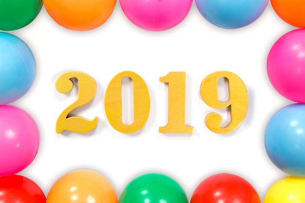 New year concept.word 2019 put on white background and the colored balls laying around.