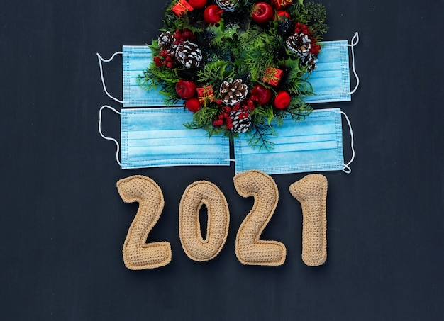 New year in the context of coronavirus knitted numbers 2021 on medical mask on chalk board