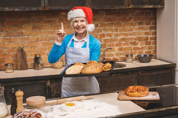 New year cooking. portrait of attractive senior aged woman is cooking on kitchen. grandmother making tasty christmas baking.