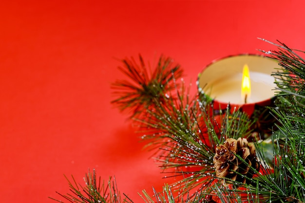 New year copyspace card. christmas tree fir branch, burning candle, decorations, on red background
