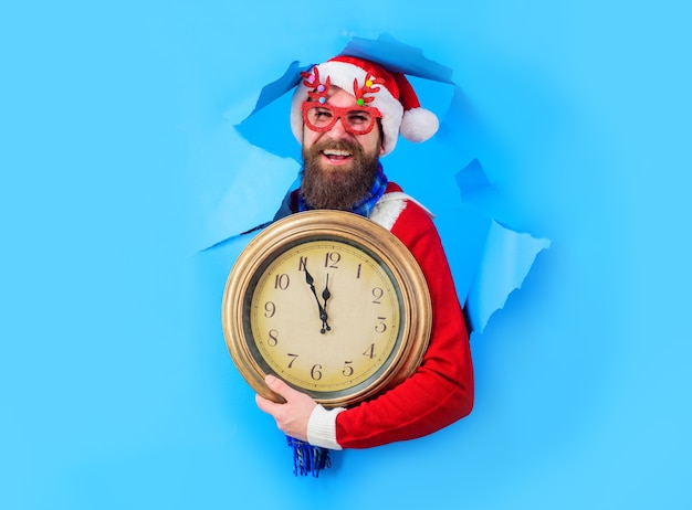 New year countdown time to celebrate time for winter party surprised santa man looks through paper h...