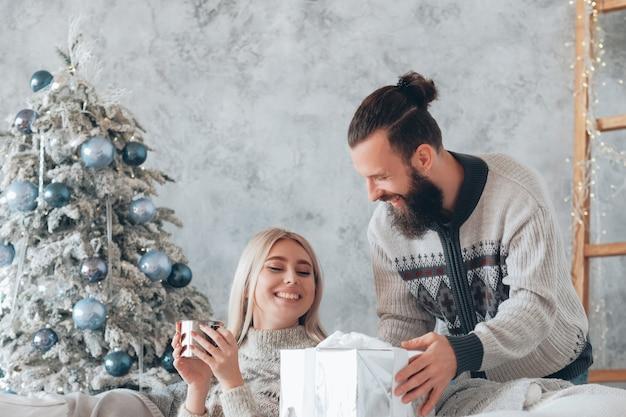 Новогодняя уютная домашняя вечеринка. парень удивил девушку подарком. леди сидит на диване с горячим напитком, улыбаясь.